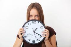 Mujer joven que sostiene los relojes de pared grandes en el fondo blanco Imágenes de archivo libres de regalías
