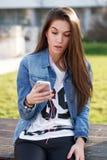 Mujer joven que sostiene smartphone Imagen de archivo libre de regalías
