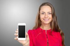 Mujer joven que sostiene smartphone Fotos de archivo
