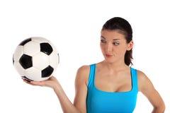 Mujer joven que sostiene un balón de fútbol con un escéptico Imágenes de archivo libres de regalías