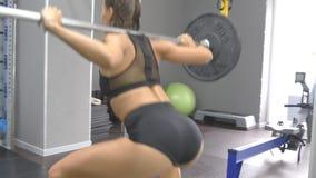 Mujer joven que sostiene un barbell con los pesos pesados en sus hombros como ella se pone en cuclillas Entrenamiento fuerte de l metrajes