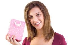 Mujer joven que sostiene un bolso rosado del regalo que sonríe en la cámara Fotografía de archivo libre de regalías