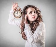 Mujer joven que sostiene un despertador imagenes de archivo