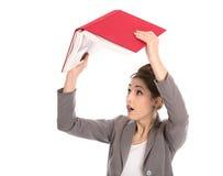 Mujer joven que sostiene un libro rojo en sus manos. Fotografía de archivo