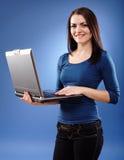 Mujer joven que sostiene un ordenador portátil Imágenes de archivo libres de regalías