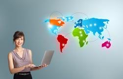 Mujer joven que sostiene un ordenador portátil y que presenta el mapa del mundo colorido Imagenes de archivo