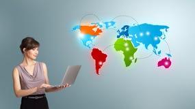Mujer joven que sostiene un ordenador portátil y que presenta el mapa del mundo colorido Foto de archivo