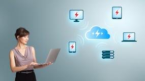 Mujer joven que sostiene un ordenador portátil y que presenta el netw computacional de la nube Foto de archivo libre de regalías