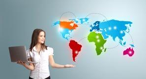 Mujer joven que sostiene un ordenador portátil y que presenta el mapa del mundo colorido Imagen de archivo libre de regalías