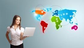 Mujer joven que sostiene un ordenador portátil y que presenta el mapa del mundo colorido Foto de archivo libre de regalías