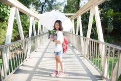 Mujer joven que sostiene un paraguas blanco. Imagen de archivo