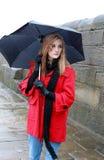 Mujer joven que sostiene un paraguas del aguanieve y de la lluvia Fotos de archivo