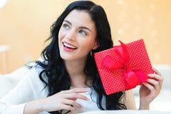 Mujer joven que sostiene un rectángulo de regalo fotos de archivo libres de regalías
