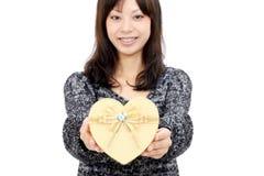Mujer joven que sostiene un rectángulo de regalo Foto de archivo libre de regalías