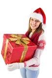 Mujer joven que sostiene un regalo mientras que sonríe en la cámara Imagenes de archivo