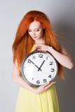 Mujer joven que sostiene un reloj grande Imagen de archivo