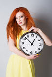 Mujer joven que sostiene un reloj grande Foto de archivo