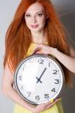 Mujer joven que sostiene un reloj grande Foto de archivo libre de regalías