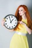 Mujer joven que sostiene un reloj grande Fotografía de archivo libre de regalías