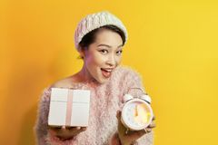 Mujer joven que sostiene un reloj que muestra casi 12 fotografía de archivo libre de regalías