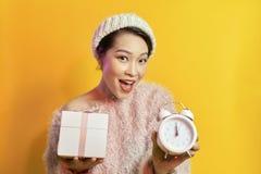 Mujer joven que sostiene un reloj que muestra casi 12 foto de archivo libre de regalías