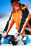 mujer joven que sostiene un snowboard Fotos de archivo