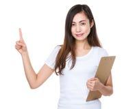 Mujer joven que sostiene un tablero y un finger que destacan Imagen de archivo libre de regalías