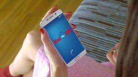 Mujer joven que sostiene un teléfono celular con la carga de Baidu app móvil Cgi conceptual del editorial Fotos de archivo