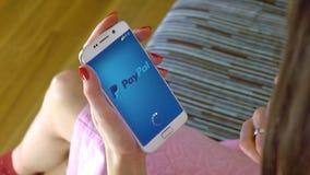 Mujer joven que sostiene un teléfono celular con la carga de Paypal app móvil Clip conceptual del editorial 4K almacen de metraje de vídeo
