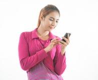Mujer joven que sostiene un teléfono elegante aislado Imagen de archivo
