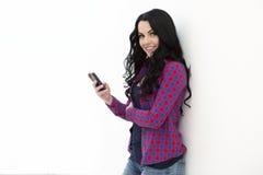 Mujer joven que sostiene un teléfono elegante mientras que envío de mensajes de texto Foto de archivo libre de regalías