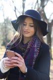 Mujer joven que sostiene un teléfono móvil disponible Imágenes de archivo libres de regalías