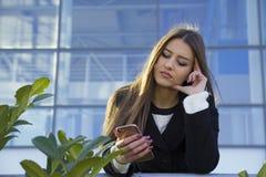 Mujer joven que sostiene un teléfono móvil disponible Fotografía de archivo