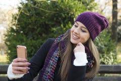 Mujer joven que sostiene un teléfono móvil disponible Imagen de archivo