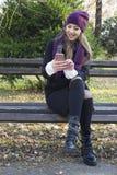 Mujer joven que sostiene un teléfono móvil disponible Imagen de archivo libre de regalías