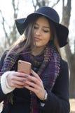 Mujer joven que sostiene un teléfono móvil disponible Fotos de archivo