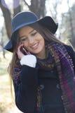Mujer joven que sostiene un teléfono móvil disponibles y los teléfonos Foto de archivo libre de regalías
