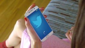 Mujer joven que sostiene un teléfono celular con la carga de Twitter app móvil Cgi conceptual del editorial Fotos de archivo libres de regalías