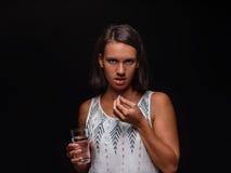 Mujer joven que sostiene un vidrio de agua y que toma píldoras en un fondo negro Ayuda médica, concepto de la medicina Copie el e Fotografía de archivo