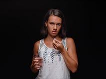 Mujer joven que sostiene un vidrio de agua y que toma píldoras en un fondo negro Ayuda médica, concepto de la medicina Copie el e Fotos de archivo libres de regalías