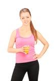 Mujer joven que sostiene un vidrio de zumo de naranja Fotografía de archivo libre de regalías