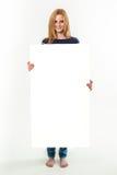 Mujer joven que sostiene una bandera en blanco Fotos de archivo libres de regalías