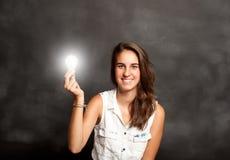 Mujer joven que sostiene una bombilla Fotografía de archivo libre de regalías