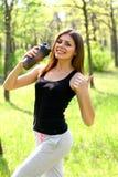 Mujer joven que sostiene una botella de agua y que muestra los pulgares para arriba Foto de archivo