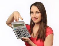 Mujer joven que sostiene una calculadora fotos de archivo libres de regalías