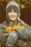 Mujer joven que sostiene una cesta de calabazas Imagenes de archivo