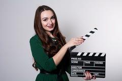 Mujer joven que sostiene una chapaleta de la película Fotos de archivo