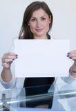 Mujer joven que sostiene una hoja de papel en blanco Foto de archivo libre de regalías