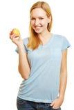 Mujer joven que sostiene una manzana Fotos de archivo libres de regalías