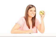 Mujer joven que sostiene una manzana y que se sienta en la tabla Fotos de archivo